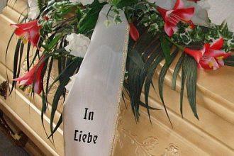 Trauergesteck aus roten Lilien mit Schleife auf einem Sarg