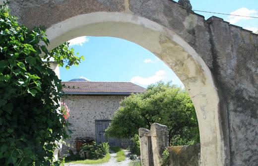 gemauerter Torbogen mit Blick in einen Innenhof